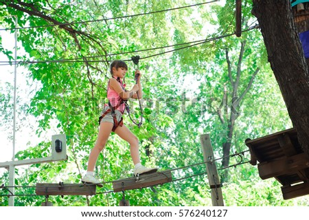 adventure climbing high wire park - hiking in the rope park girl in safety equipment #576240127