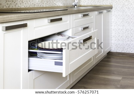Opened kitchen drawer with plates inside, a smart solution for kitchen storage and organizing.  Royalty-Free Stock Photo #576257071