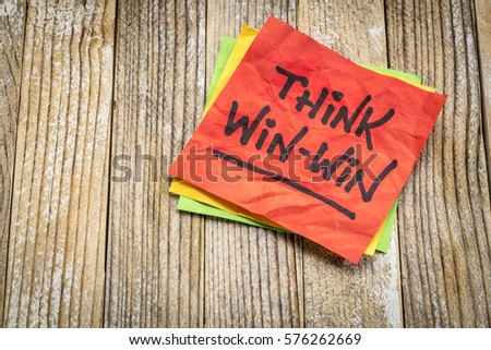 Think win-win concept  - handwriting on a sticky note against grunge wood board #576262669