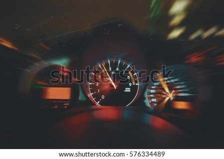 Sports Car Drives Fast at Night, Shows Interior of Car Including Speedometer and Tachometer Royalty-Free Stock Photo #576334489