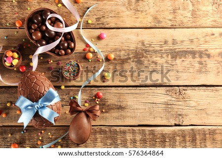Chocolate Easter eggs with color ribbon bows on wooden background Royalty-Free Stock Photo #576364864