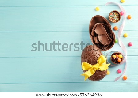Easter composition with chocolate eggs on color wooden background, space for text Royalty-Free Stock Photo #576364936