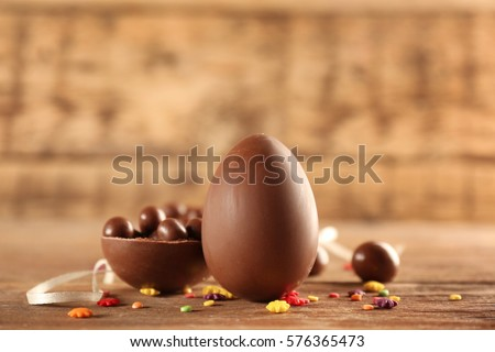 Chocolate Easter eggs and candies on wooden background Royalty-Free Stock Photo #576365473