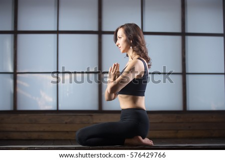 Young attractive woman practicing yoga, sitting in vajrasana exercise, seiza pose with namaste, working out, wearing sportswear, black tank top, pants, indoor full length, studio evening practice  #576429766
