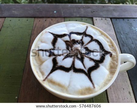 cappuccino  coffee and milk foam and chocolate topping on wooden table #576487606