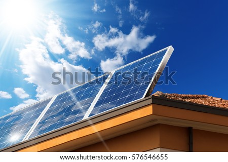 Close-up of a house roof with a solar panels on top, on a blue sky with clouds and sun rays Royalty-Free Stock Photo #576546655