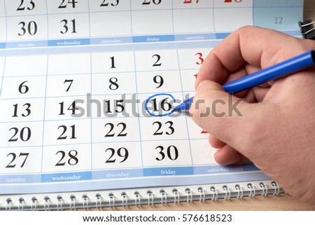 hand marks the date on  calendar in blue #576618523