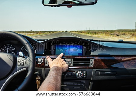 Man behind the wheel of his car reaches out to touch the screen of his GPS navigation system. #576663844