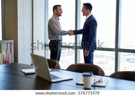 Two smiling businessmen shaking hands together while standing by windows in an office boardroom overlooking the city  #576771979