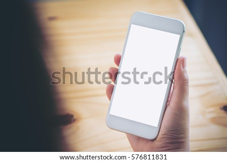 Mockup image of hand holding white mobile phone with blank white screen on vintage wood table in cafe #576811831