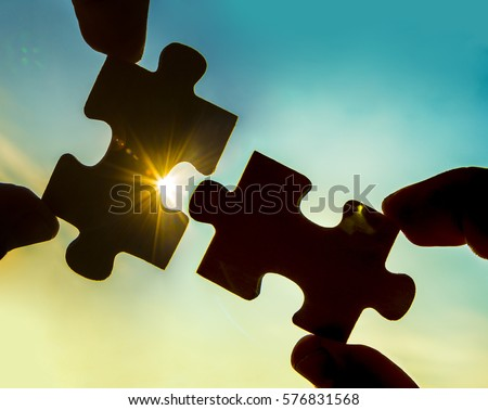 two hands trying to connect couple puzzle piece with sunset background. Jigsaw alone wooden puzzle against sun rays. one part of whole. symbol of association and connection. business strategy. Royalty-Free Stock Photo #576831568