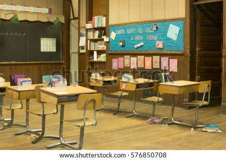 Old fashioned school room with desks and books and papers and blackboard #576850708