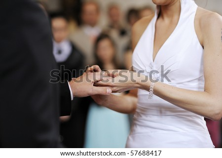 Bride putting a wedding ring on a groom's finger #57688417