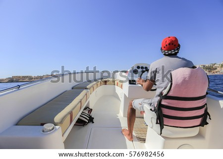 Man driving motor boat. Boating on the sea. Fast motor boat #576982456