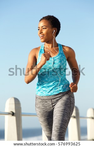 Portrait of active young woman running and listening to music with earphones #576993625