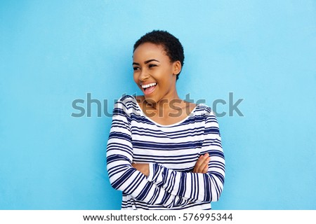 Portrait of cool young black woman laughing against blue wall #576995344