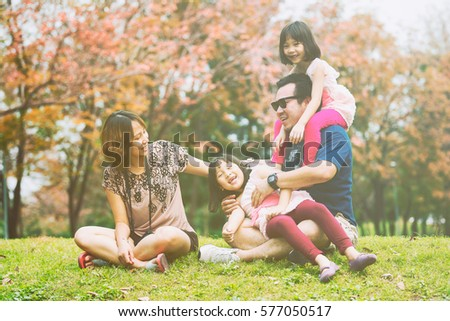 Asian family playing together on grass in park #577050517