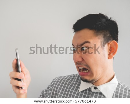 Asian man being shouted from the boss in the smartphone. #577061473