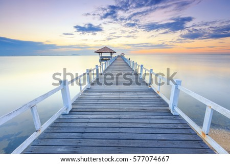 Old wood bridge pier  against beautiful sunset sky use for natural background ,backdrop and multipurpose sea scene #577074667