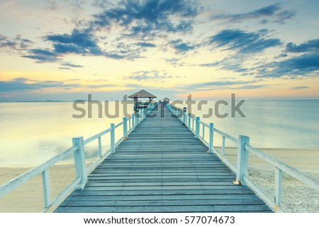 Old wood bridge pier  against beautiful sunset sky use for natural background ,backdrop and multipurpose sea scene #577074673