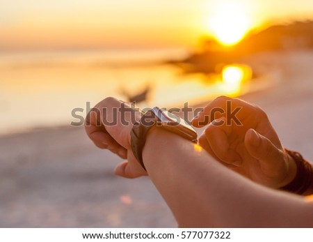 Smart watch woman using smartwatch touching button and touchscreen on active sports activity or morning jogging during beach sunrise or sunset. Closeup of hands and wrist with smart watch screen. #577077322