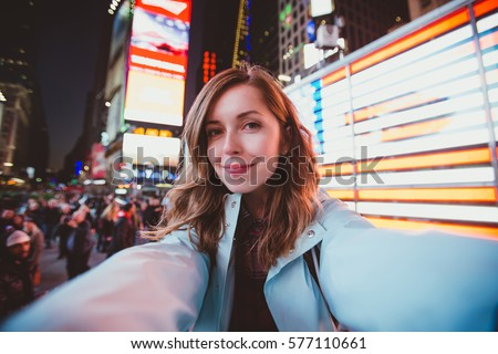 Young happy woman taking selfie on Times Square at night, Manhattan. Inspiring New York atmosphere and a beautiful smiling girl.