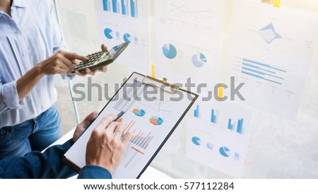 Business man analysis data document with blurred accountant calculating Royalty-Free Stock Photo #577112284