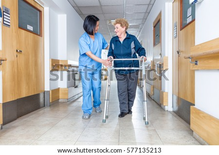 Senior female patient being assisted by female asian nurse in using walker.