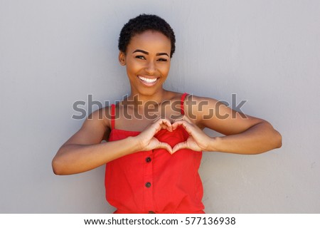 Portrait of smiling young african american woman with heart shape hand sign  #577136938