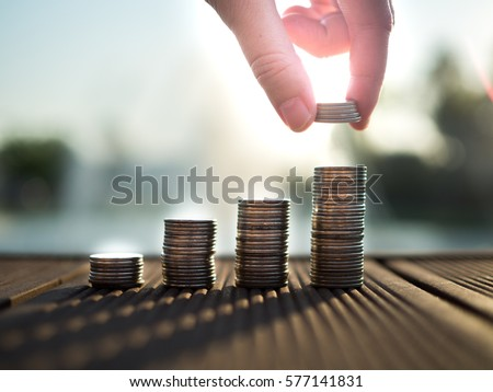 Hand putting money coins stack growing, saving money for purpose concept Royalty-Free Stock Photo #577141831