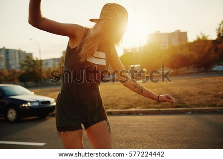 Beautiful young girl with tattoos riding on his longboard on the road in the city in sunny weather. Extreme sports. Rear view of motion #577224442