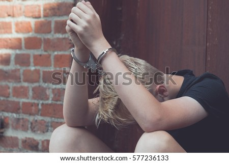 Dejected teenage boy held captive in handcuffs sitting on the ground against an exterior wooden door with his head down between his legs after being busted and arrested Royalty-Free Stock Photo #577236133