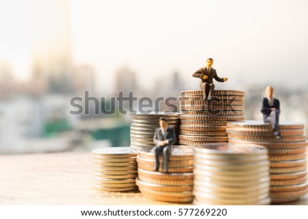Miniature people: Small businessmen sitting on stack of coins, Money, Financial, Business Growth concept. Royalty-Free Stock Photo #577269220