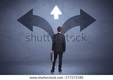 Businessman taking a decision while looking at arrows on the wall concept background #577272580