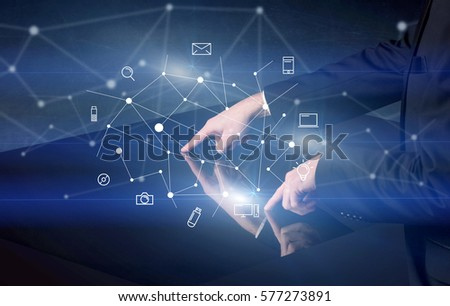 Male hands touching interactive table with blue mixed communication icons in the background #577273891