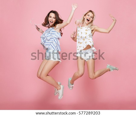Two happy carefree young women jumping and listening to music from cell phones over pink background #577289203