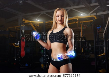 Strong sporty woman bodybuilder with tanned body doing exercises with dumbbell in the gym. Sports and fitness. Neon dumbbells #577317184