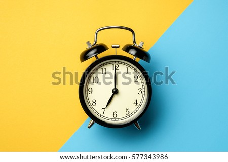 black vintage alarm clock on two tone color yellow and light blue background