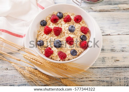 Porridge being garnished with fresh berries blueberries and raspberry #577344322