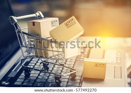 Paper boxes in a shopping cart on a laptop keyboard. Ideas about e-commerce, e-commerce or electronic commerce is a transaction of buying or selling goods or services online over the internet. #577492270