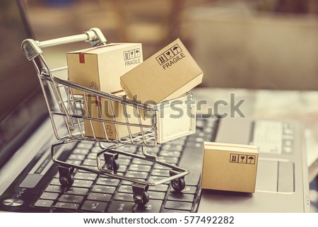 Paper boxes in a shopping cart on a laptop keyboard. Ideas about e-commerce, e-commerce or electronic commerce is a transaction of buying or selling goods or services online over the internet. Royalty-Free Stock Photo #577492282