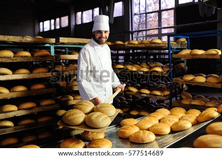 young cute baker smiling pulls out of the oven fresh bread shovel bread #577514689