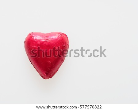Heart shape chocolate wrapped in red foil isolated over white background #577570822
