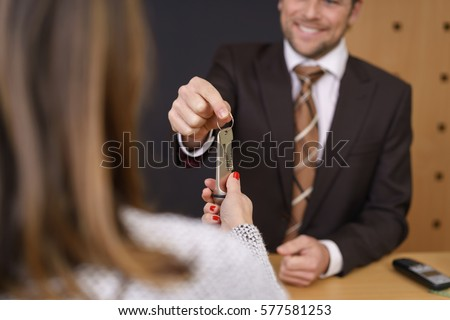 Smiling hotel manager handing over a door key to a woman customer after checking her in to the hotel, selective focus to his hand and the key #577581253