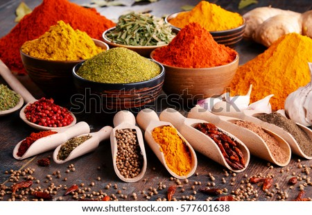 Variety of spices and herbs on kitchen table. Royalty-Free Stock Photo #577601638