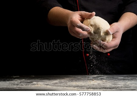 Dough in chef hand on a dark black background of wood. Baking bread, pizza, pasta. Recipe from chef cooks pizza. Italian home cooking. Horizontal photo with text area space for menu design  #577758853