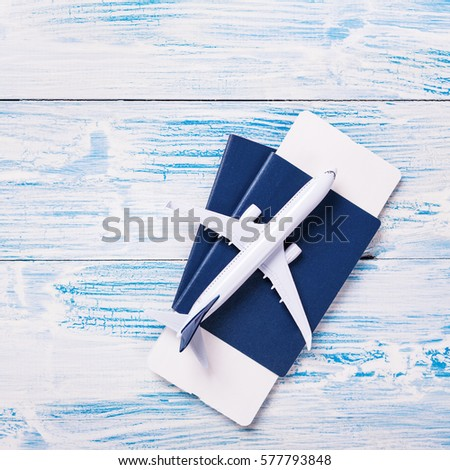 White blank model of passenger plane on passports with boarding pass on blue rustic wooden background #577793848