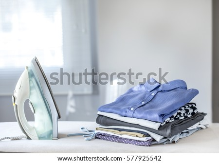 Ironing clothes on ironing board Royalty-Free Stock Photo #577925542