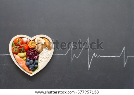 Healthy food in heart and cardiograph on blackboard medical abstract concept Royalty-Free Stock Photo #577957138