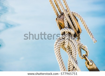 Sailing boat pulley, block and tackle with moored nautical rope. Royalty-Free Stock Photo #577965751